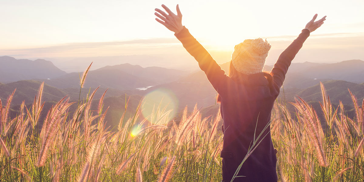Carefree woman in meadow with financial freedom